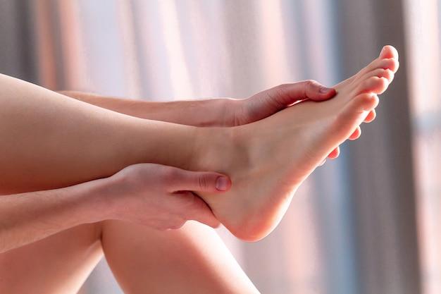 Giovane che fa un massaggio rilassante ai piedi a casa sul letto dopo una lunga e dura giornata di lavoro. terapia manuale. terapia del dolore, affaticamento e disagio alle gambe