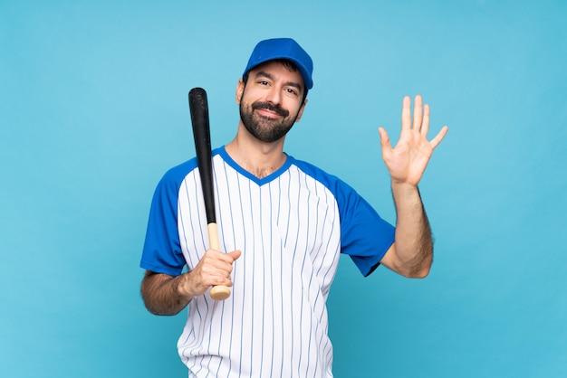 Giovane che gioca a baseball sopra il saluto blu isolato con la mano con l'espressione felice
