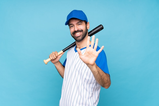 Giovane che gioca a baseball sopra la parete blu isolata che conta cinque con le dita