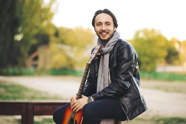 Giovane che gioca alla chitarra nel lago
