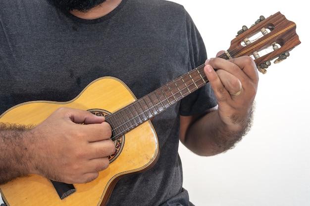 Giovane che gioca ukulele con camicia e pantaloni neri.