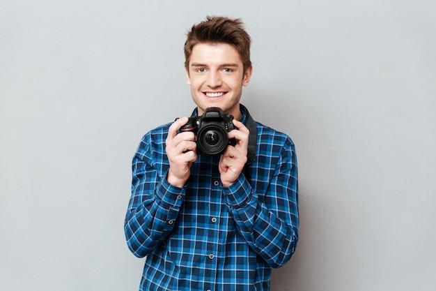 Giovane che giudica la sua macchina fotografica in mani isolate