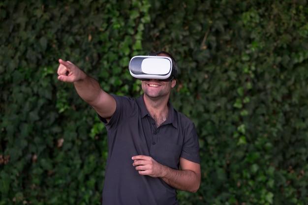 Giovane che gode della cuffia avricolare di vetro di realtà virtuale o degli occhiali 3d