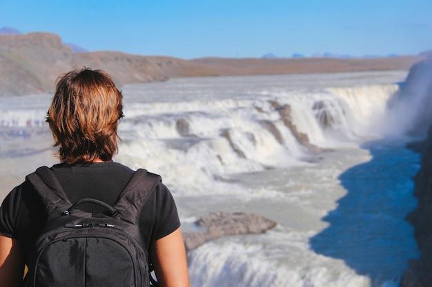 Giovane che guarda le cascate in islanda