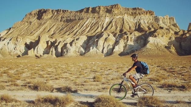 Giovane che guida una bicicletta su una priorità bassa di un paesaggio con le montagne