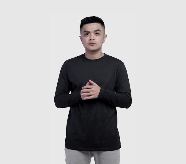 Giovane che indossa la maglietta nera a maniche lunghe isolata su bianco