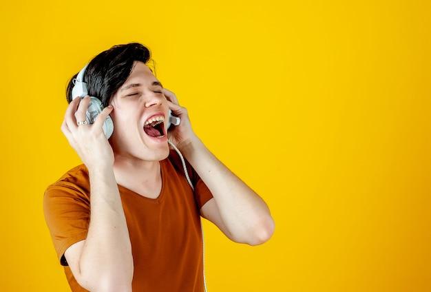 Giovane che indossa le cuffie e che gode della musica; su uno sfondo di oro giallo, le emozioni di un giovane