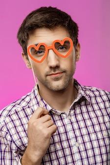 Giovane che indossa occhiali falsi sopra la parete viola. festa di compleanno.