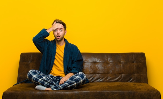Giovane che indossa un pigiama in preda al panico per una scadenza dimenticata sentendosi stressato dover nascondere un disordine o un errore. seduto su un divano