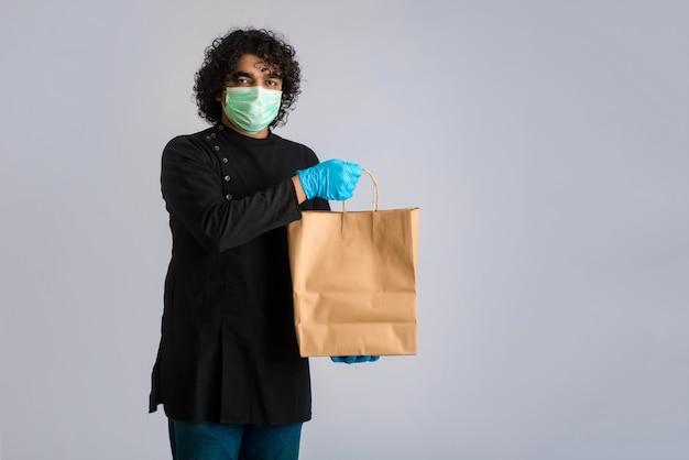 Giovane che indossa una maschera di protezione medica che tiene e che mostra sacco di carta.
