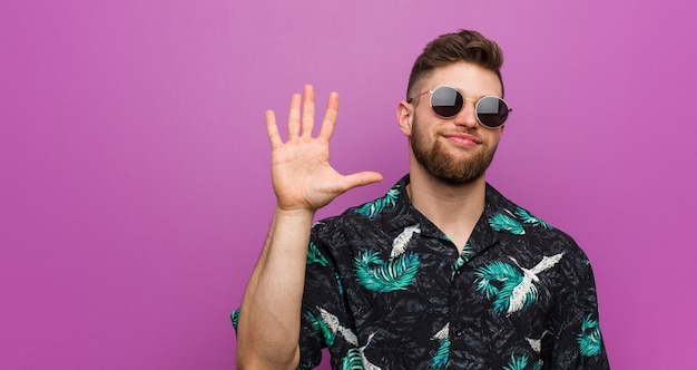 Giovane che indossa una vacanza sembrare sorridente allegro mostrando il numero cinque con le dita.
