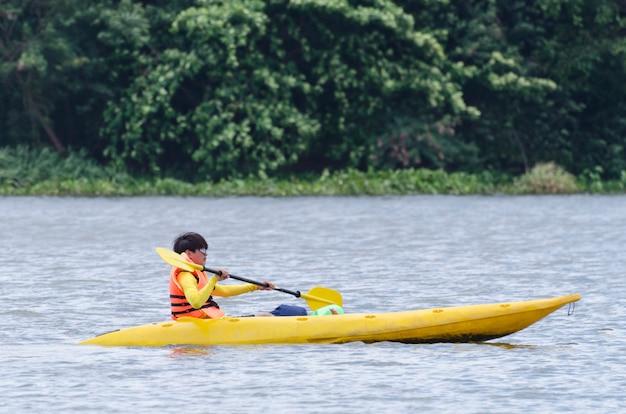 Giovane che kayaking su un lago