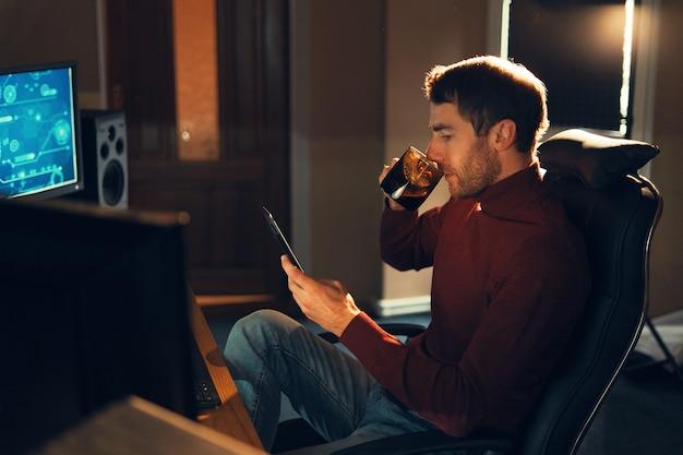 Giovane che lavora a casa usando uno smartphone e un computer.
