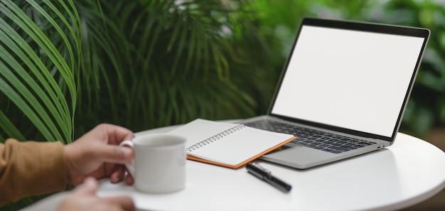 Giovane che lavora al suo progetto con il computer portatile mentre beve una tazza di caffè nel posto di lavoro comodo all'aperto