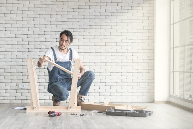 Giovane che lavora come tuttofare, montaggio tavolo in legno con attrezzature