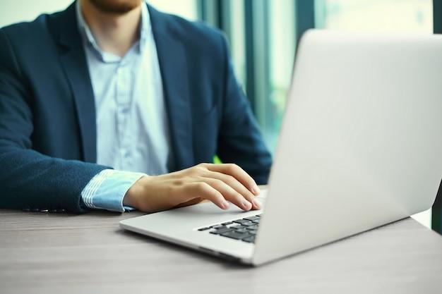 Giovane che lavora con il computer portatile, le mani dell'uomo sul computer portatile, uomo d'affari nel luogo di lavoro