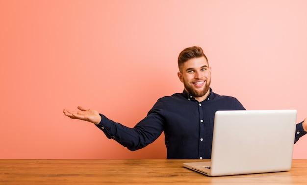 Giovane che lavora con il suo computer portatile che mostra un'espressione benvenuta.