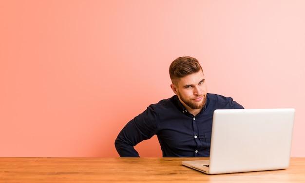 Giovane che lavora con il suo computer portatile che rimprovera qualcuno molto arrabbiato.
