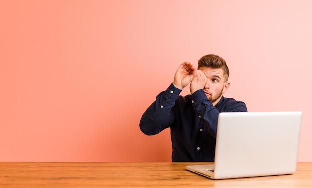 Giovane che lavora con il suo computer portatile che sembra lontano tenendolo mano sulla fronte.