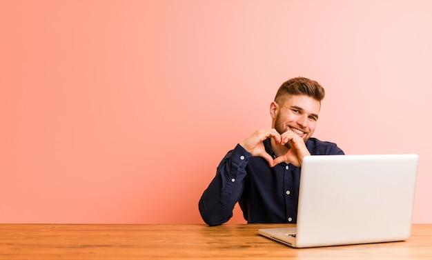 Giovane che lavora con il suo computer portatile che sorride e che mostra una forma del cuore con lui mani.