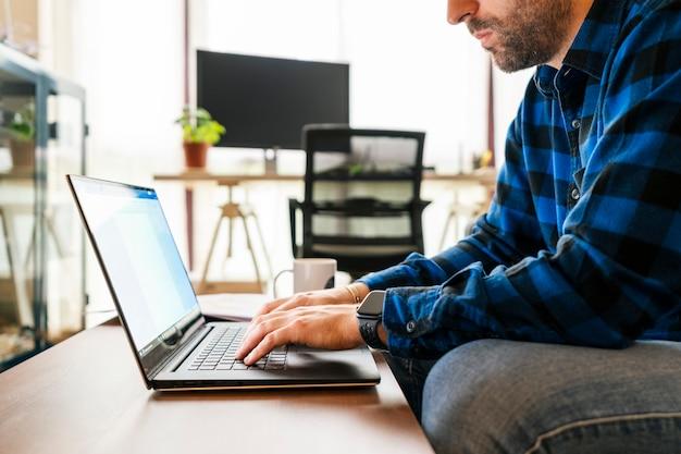 Giovane che lavora con il suo computer portatile dal suo salone. resta a casa, lavora da casa concetto