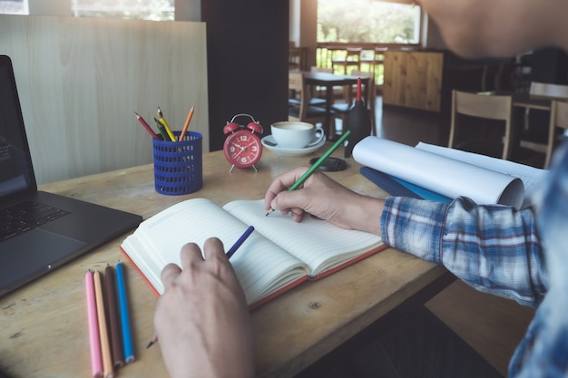 Giovane che lavora con la matita di colore e computer portatile del taccuino e del computer