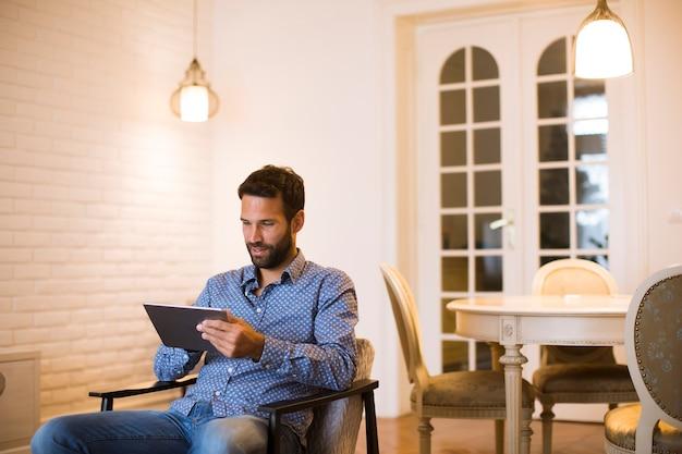 Giovane che lavora da casa sulla tavoletta digitale