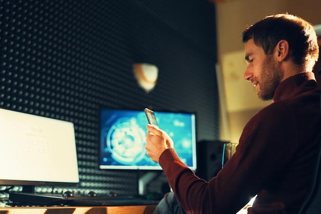 Giovane che lavora in studio utilizzando uno smartphone e un computer.