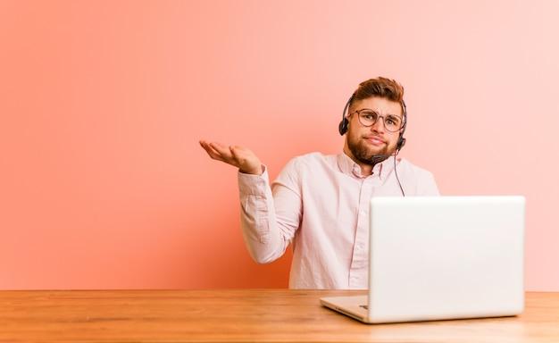 Giovane che lavora in un call center dubitando tra due opzioni.