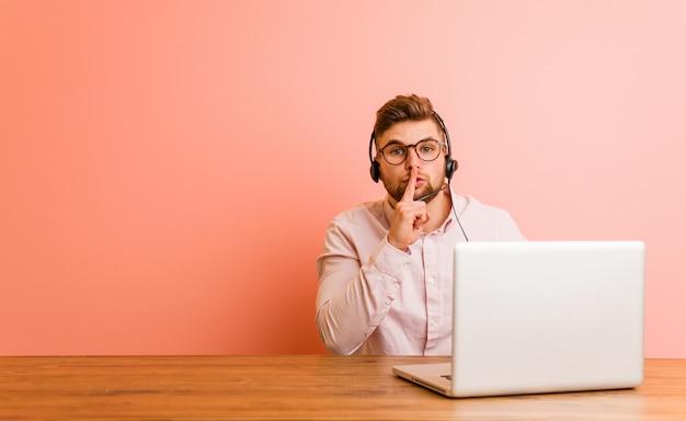 Giovane che lavora in un call center mantenendo un segreto o chiedendo silenzio.