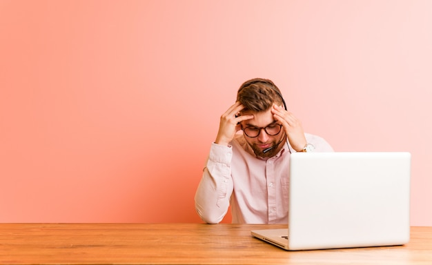Giovane che lavora in un call center toccando le tempie e avendo mal di testa.