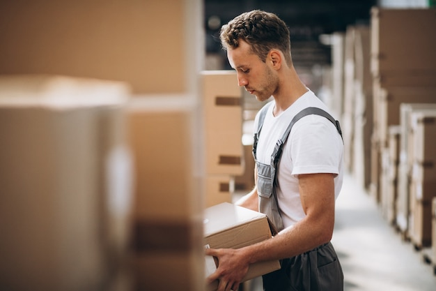 Giovane che lavora in un magazzino con scatole