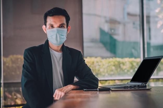 Giovane che lavora su un computer portatile con una maschera protettiva