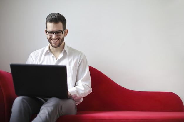 Giovane che lavora su un computer portatile su un divano