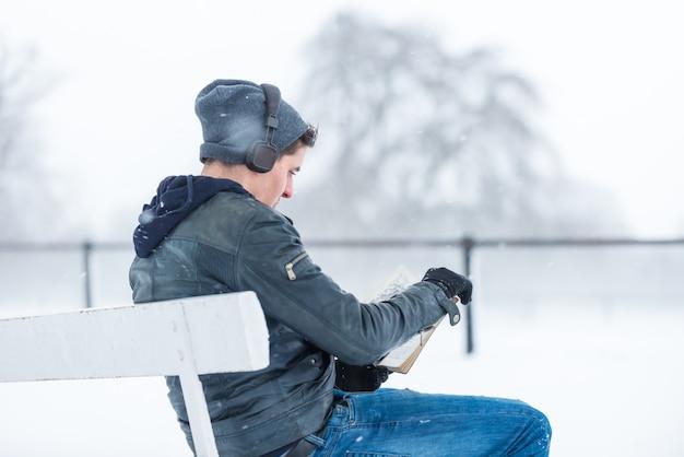 Giovane che legge e che ascolta musica in un giorno nevoso.