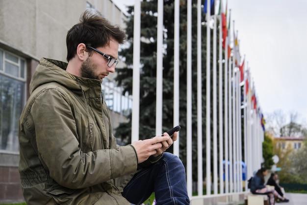 Giovane che manda un sms in un telefono cellulare che si siede su un banco nel quadrato
