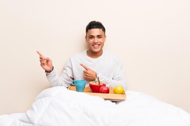 Giovane che mangia prima colazione a letto che indica dito il lato