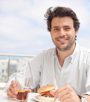 Giovane che mangia un hamburguer