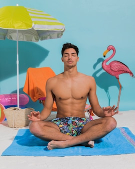 Giovane che medita su spiaggia decorativa