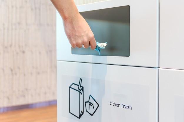 Giovane che mette sacchetto di plastica nel recipiente di riciclaggio nell'aeroporto.