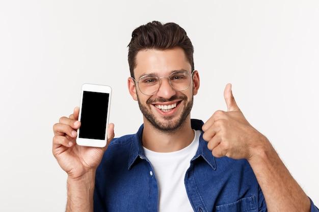Giovane che mostra uno schermo in bianco dello smart phone con i pollici in su isolati su un bianco.