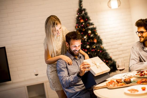 Giovane che ottiene presente dalla donna amorevole per natale o capodanno