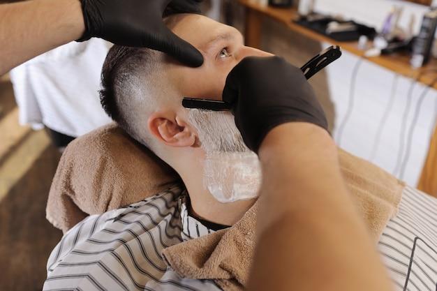 Giovane che ottiene una rasatura antiquata con il rasoio diritto