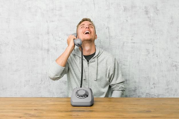 Giovane che parla su un telefono vintage rilassato e felice ridendo, collo allungato mostrando i denti.