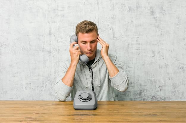 Giovane che parla sulle tempie commoventi di un telefono dell'annata e che ha mal di testa.