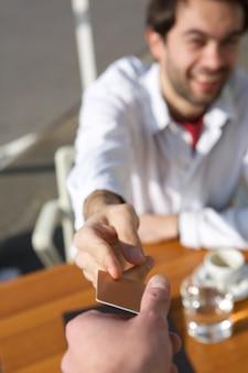 Giovane che passa una carta di pagamento del cameriere al ristorante
