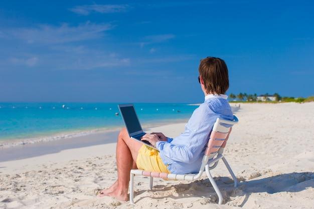 Giovane che per mezzo del computer portatile sulla spiaggia tropicale
