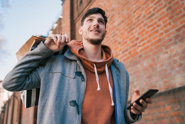 Giovane che per mezzo del suo telefono cellulare sulla via.