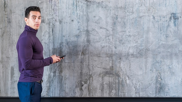 Giovane che per mezzo del telefono cellulare che esamina macchina fotografica che sta contro la parete grigia concreta
