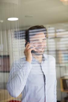 Giovane che per mezzo del telefono cellulare dietro il vetro nell'ufficio